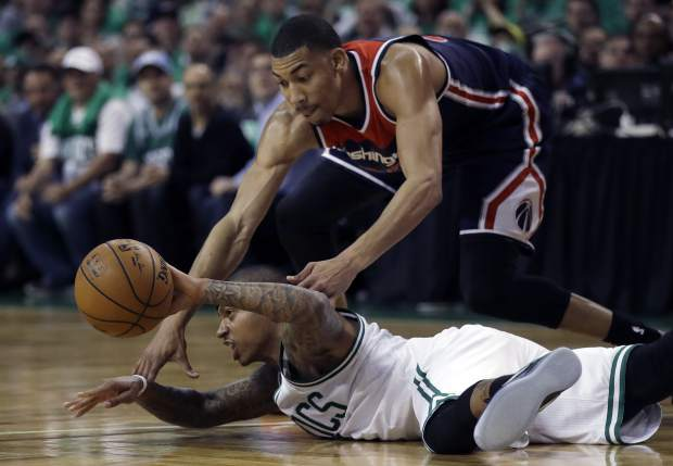 Boston Celtics guard Isaiah Thomas makes a pass while sprawled on the floor as Washington Wizards forward Otto Porter Jr., top, defends during the second quarter of Game 7 of a second-round NBA basketball playoff series, Monday, May 15, 2017, in Boston. (AP Photo/Charles Krupa)