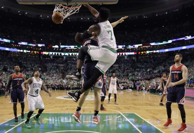 Boston Celtics forward Jaylen Brown (7) dunks over Washington Wizards guard Bojan Bogdanovic during the fourth quarter of Game 7 of a second-round NBA basketball playoff series, Monday, May 15, 2017, in Boston. (AP Photo/Charles Krupa)