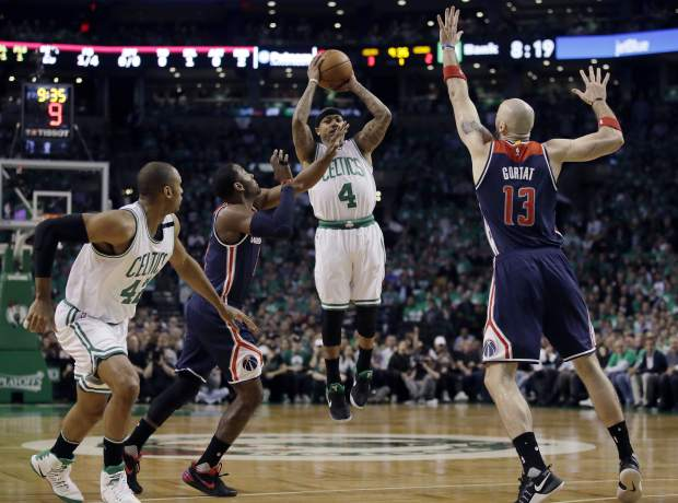 Boston Celtics guard Isaiah Thomas (4) shoots between Washington Wizards guard John Wall, left, and Wizards center Marcin Gortat (13) during the first quarter of Game 7 of a second-round NBA basketball playoff series, Monday, May 15, 2017, in Boston. (AP Photo/Charles Krupa)