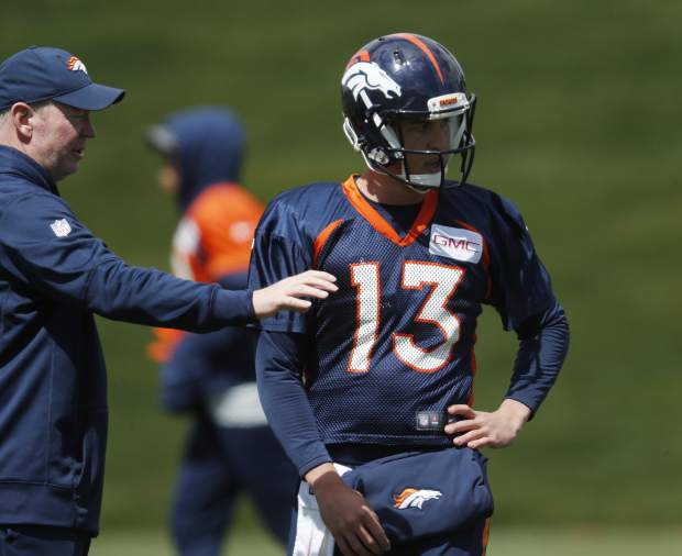 Denver Broncos quarterbacks coach Bill Musgrave, left, confers with quarterback Trevor Siemian during a drill at NFL football organized team activities at the team's headquarters Tuesday, May 23, 2017, in Englewood, Colo. (AP Photo/David Zalubowski)