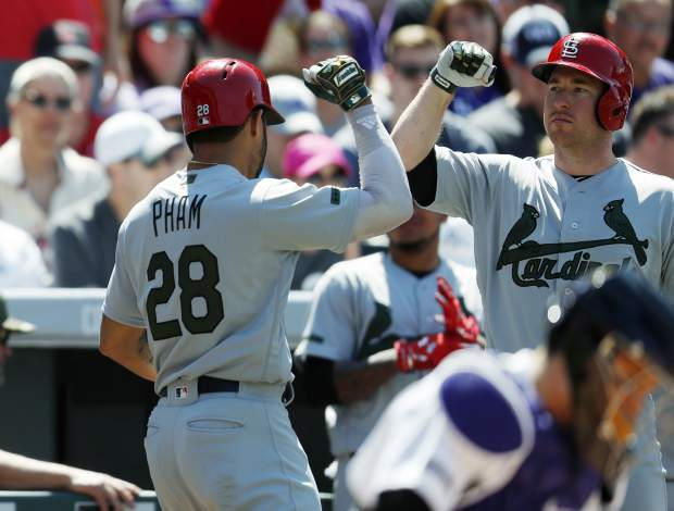 St. Louis Cardinals' Tommy Pham, left, is congratulated by Jedd Gyorko after hitting a solo home run in the seventh inning of a baseball game Sunday, May 28, 2017, in Denver. (AP Photo/David Zalubowski)