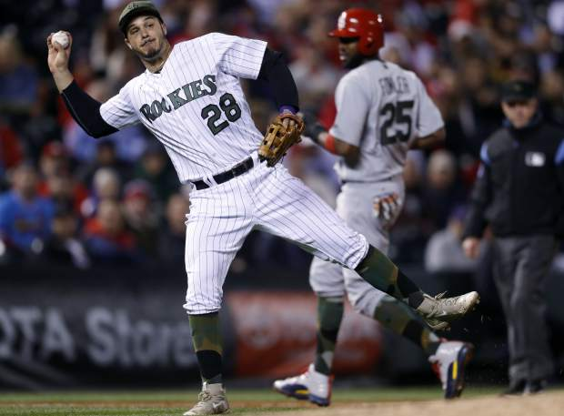 Colorado Rockies third baseman Nolan Arenado throws to first base to put out St. Louis Cardinals' Yadier Molina to end the top of the ninth inning of a baseball game Saturday, May 27, 2017, in Denver. The Cardinals won 3-0. (AP Photo/David Zalubowski)