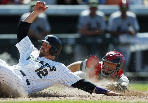 Colorado Rockies' Mark Reynolds, left, scores on sacrifice fly as St. Louis Cardinals catcher Eric Fryer misses the tag in the eighth inning of a baseball game Sunday, May 28, 2017, in Denver. (AP Photo/David Zalubowski)