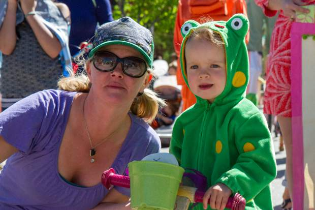 Two-year-old Selah Gorman and Kelly LeMere watch the Ngoma Drum and Dance Ensemble during the 2017 Carbondale Dandelion Parade.