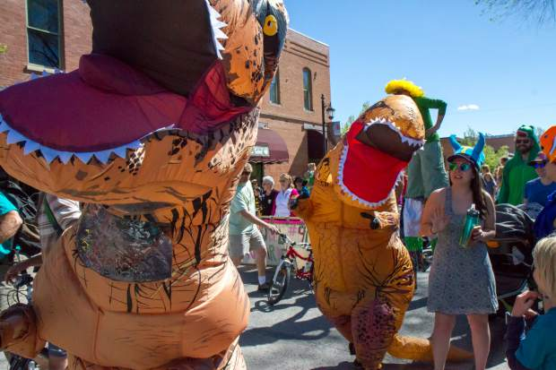A pair of t-rexes raid the 2017 Carbondale Dandelion Parade down Main Street on Saturday monring. The Ngoma drum and dance ensemble lead this years parade while entertaining the crowd with dances and live music. For more photos from the parade and park go to postindependent.com