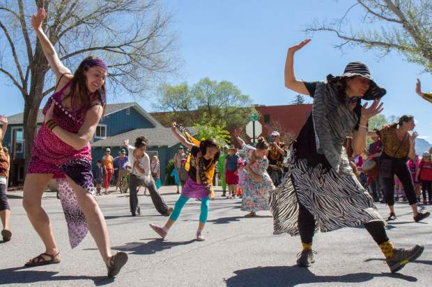 Leeza Monge, left, leads the Ngoma Drum and Dance Ensemble down main street for the Carbondale Dandelion Parade.