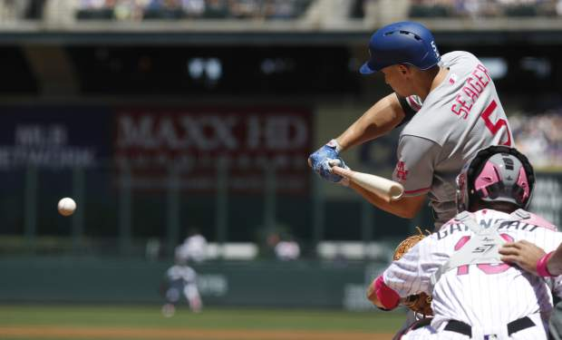 Los Angeles Dodgers' Corey Seager, top, starts his swing before connecting for a two-run home run as Colorado Rockies catcher Dustin Garneau waits for the pitch in the first inning of a baseball game Sunday, May 14, 2017, in Denver. (AP Photo/David Zalubowski)