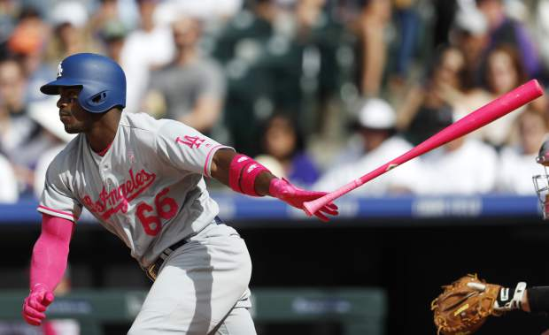 Los Angeles Dodgers' Yasiel Puig follows the flight of his single off Colorado Rockies relief pitcher Adam Ottavino in the eighth inning of a baseball game Sunday, May 14, 2017, in Denver. (AP Photo/David Zalubowski)
