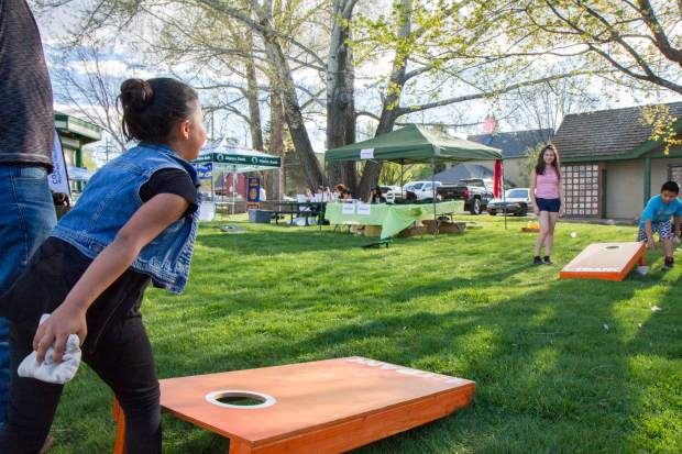 Eight-year-old Camilla Zapata plays a round of corn hole with friends Jasiel Martinez, 9, and Citlali Torrez, 13, at the Festival Las Americas on Friday evening.