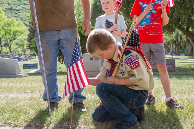 David Williams places a flag on the gravesite of a U.S. servicemember at Rosebud Cemetary in Glenwood Springs.