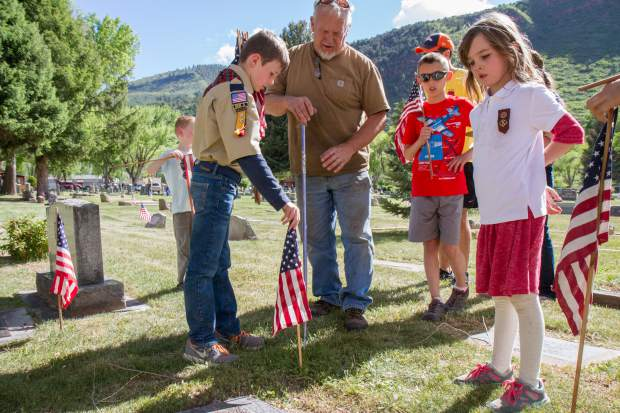 Members of boy scout troop 225 and girl scout Victoria Williams, right, place flags on with the graves of military servicemen and women at Rosebud cemetary in Glenwood .