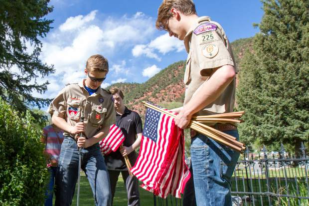 Members of boy scout troop 225 place flags with the graves of military servicemen and women at Rosebud cemetary in Glenwood .