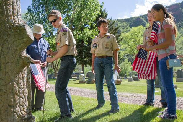 Members of Boy Scout Troop 225 and Cate Williams, right, place flags with the graves of military servicemen and women at Rosebud Cemetery in Glenwood Springs. The traditional Memorial Day ceremonies take place at 11 a.m. Monday at the cemetery, featuring keynote speaker retired U.S. Air Force veteran Greg Rosenmerkel of Glenwood. Carbondale's American Legion Post 100 also has its traditional wreath ceremony at 10 a.m. Monday at the Veterans Memorial Bridge (Colorado 133), followed by a Memorial Day observance at Evergreen Cemetery at 11.