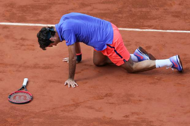 FILE - In this June 2, 2015, file photo, Switzerland's Roger Federer gets up after slipping during a quarterfinal match against Switzerland's Stan Wawrinka at the French Open tennis tournament in Paris, France. Roger Federer says he won't play in the French Open and instead prepare to play on grass and hard courts later this season. Federer posted a message entitled
