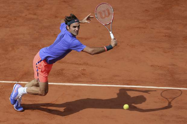 FILE - In this June 2, 2016, file photo, Switzerland's Roger Federer makes a return against Switzerland's Stan Wawrinka during a quarterfinal match at the French Open tennis tournament in Paris, France. Roger Federer says he won't play in the French Open and instead prepare to play on grass and hard courts later this season. Federer posted a message entitled
