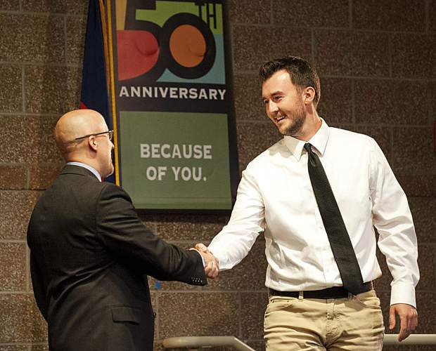 Stu Curry, at left, associate professor at CMC's Colorado Law Enforcement Training Academy, congratulates graduate Quinton Wheatley during the commencement ceremony Friday.