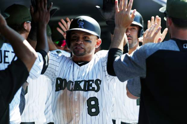 Colorado Rockies' Gerardo Parra, center, is congratulated after scoring with Ian Desmond on a single hit by Tony Wolters in the eighth inning of a baseball game Sunday, May 28, 2017, in Denver. (AP Photo/David Zalubowski)