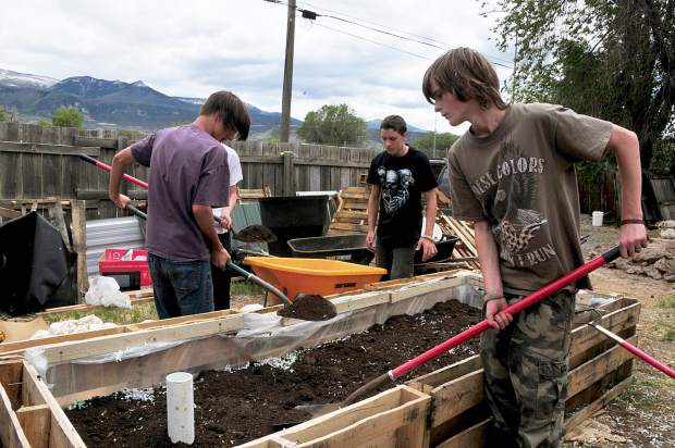Tim Cook, foreground, Shane Scott, left, and Gaibrial Winters are three Yampah Mountain HIgh School students that are helping to ensure that the Parachute community has fresh produce and vegetables this summer.
