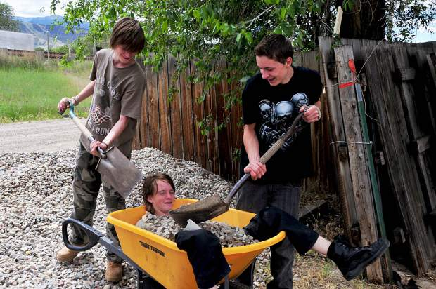 Aidan Cook has fun being covered in rocks by his twin Tim and Gaibrial Winters on the right while helping to build the Parachute LIFT-UP gardens.