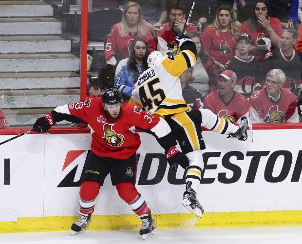 Ottawa Senators defenseman Fredrik Claesson (33) collides with Pittsburgh Penguins right wing Josh Archibald (45) during the third period of game six of the Eastern Conference final in the NHL Stanley Cup hockey playoffs in Ottawa on Tuesday, May 23, 2017. (Sean Kilpatrick/The Canadian Press via AP)