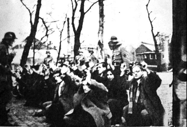 Jewish people are lined up for inspection by German soldiers.