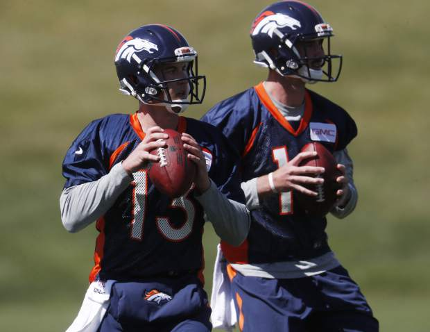 FILE - In this April 27, 2017, file photo, Denver Broncos quarterbacks Trevor Siemian (13) and Paxton Lynch are look to pass during a voluntary minicamp at the team' headquarters in Englewood, Colo. The Broncos, a team with a dazzling defense and ambitions of a deep playoff run, must decide which young quarterback will lead them in 2017: the gifted first rounder Paxton Lynch or the egghead seventh rounder Trevor Siemian. (AP Photo/David Zalubowski, File)