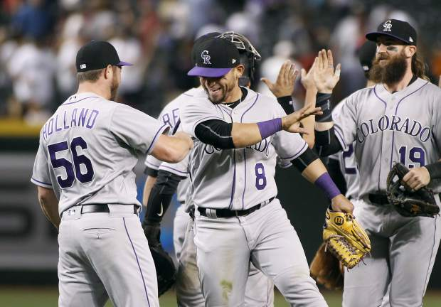 Colorado Rockies' Gerardo Parra (8) celebrates with Greg Holland (56), Charlie Blackmon (19) and other teammates after the team's 7-6 victory against the Arizona Diamondbacks during a baseball game, Saturday, April 29, 2017, in Phoenix. (AP Photo/Ralph Freso)