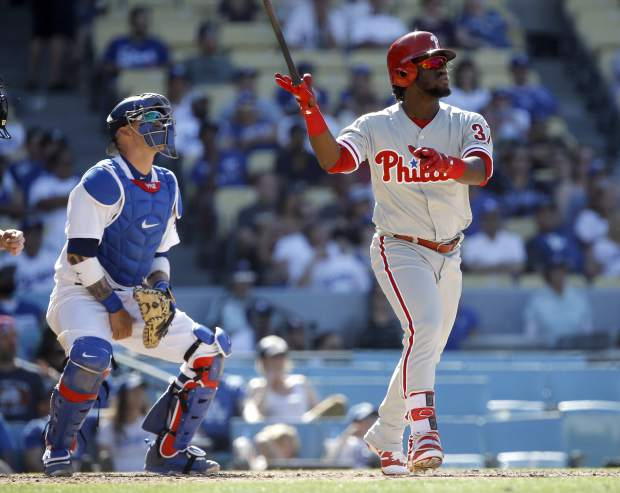 Philadelphia Phillies' Odubel Herrera, right, hits a two-run home run with Los Angeles Dodgers catcher Yasmani Grandal watching during the ninth inning of a baseball game in Los Angeles, Sunday, April 30, 2017. (AP Photo/Alex Gallardo)