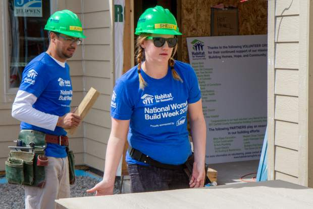 Volunteer Shelly Davies helps cut a piece of wood siding at the Silt jobsite.