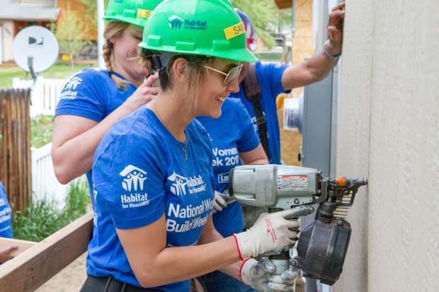 Samantha Salazar learns how to use a nail gun for the first time while volunteering during National Women Build Week.