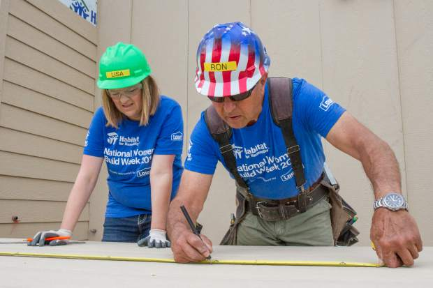Habitat for Humanity Construction Supervisor Ron Acee works with volunteer Lisa Gurule to take measurements on a piece of wood siding.