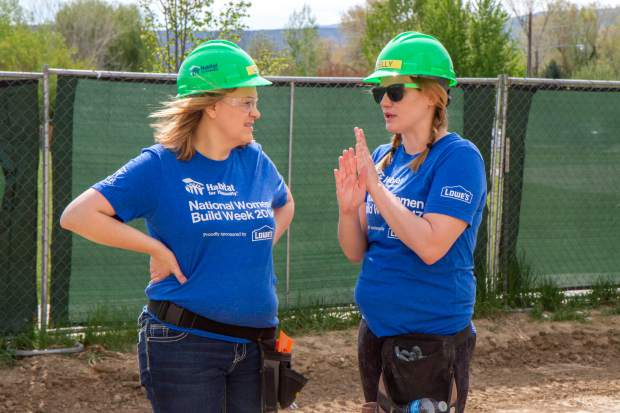 Volunteers Lisa Gurule, left, and Shelly Davies discuss the plan before cutting pieces of wood siding.