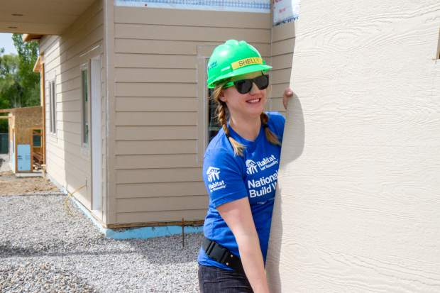 Volunteer Shelly Davies helps carry a piece of wood siding to be placed on the habitat duplex being built for two families in Silt.