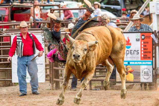 Nate Hoey holds on with all his might in hopes to get the longest bull ride during Carbondale's Wild West Rodeo last year.