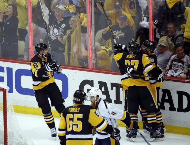 Pittsburgh Penguins' Brian Dumoulin (8) and Carter Rowney (37) celebrate with Nick Bonino after Bonino's goal against the Nashville Predators during the first period in Game 1 of the NHL hockey Stanley Cup Final, Monday, May 29, 2017, in Pittsburgh. (AP Photo/Gene J. Puskar)