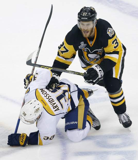 Pittsburgh Penguins' Carter Rowney (37) checks Nashville Predators' Viktor Arvidsson (38) to the ice during the first period in Game 1 of the NHL hockey Stanley Cup Final, Monday, May 29, 2017, in Pittsburgh. (AP Photo/Gene J. Puskar)
