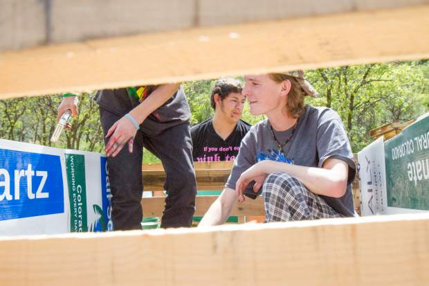 Aiden Cook works with fellow students to put up siding on the self-wicking raised bed garden near the campus greenhouse.