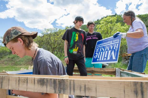 From left, Aiden Cook, Mikole Ogden and Brian Portillo work with Kim Wille, founder of Growing Empowerment, on creating the self-wicking raised bed garden entirely from scratch.