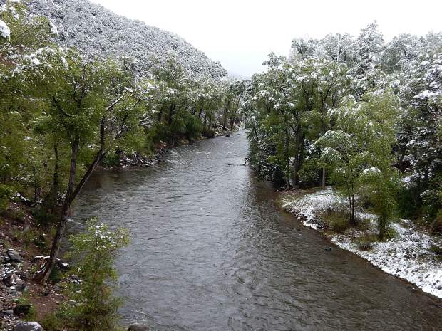 Snow covers the trees along a stretch of the Roaring Fork River in the midvalley Thursday. The storm slowed the pace of snowmelt in the high country and will likely prolong higher flows in rivers and streams.