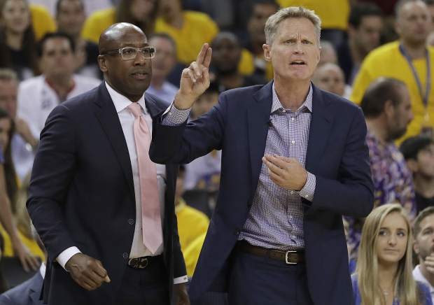 Golden State Warriors head coach Steve Kerr, right, gestures next to interim head coach Mike Brown during the first half of Game 2 of basketball's NBA Finals against the Cleveland Cavaliers in Oakland, Calif., Sunday, June 4, 2017. (AP Photo/Marcio Jose Sanchez)