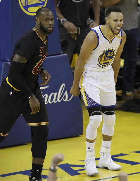 Golden State Warriors guard Stephen Curry reacts after scoring next to Cleveland Cavaliers forward LeBron James during the second half of Game 2 of basketball's NBA Finals in Oakland, Calif., Sunday.