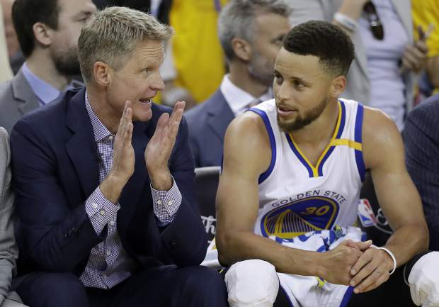 Golden State Warriors head coach Steve Kerr, left, talks with guard Stephen Curry during the second half of Game 2 of basketball's NBA Finals against the Cleveland Cavaliers in Oakland, Calif., Sunday, June 4, 2017. (AP Photo/Marcio Jose Sanchez)