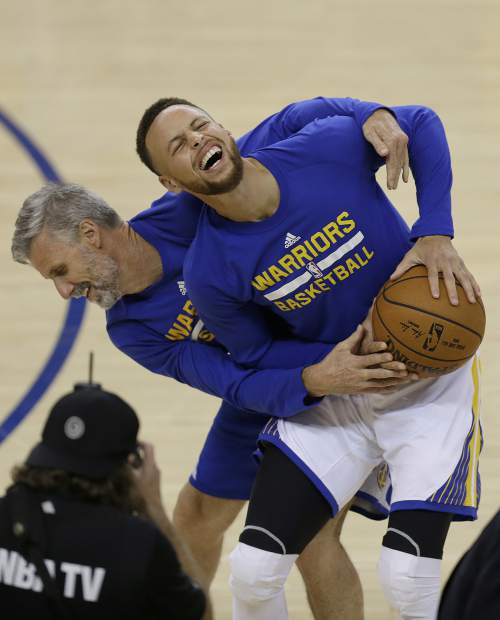 Golden State Warriors guard Stephen Curry, right, laughs while warming up with assistant coach Bruce Fraser before Game 5 of basketball's NBA Finals between the Warriors and the Cleveland Cavaliers in Oakland, Calif., Monday, June 12, 2017. (AP Photo/Ben Margot)