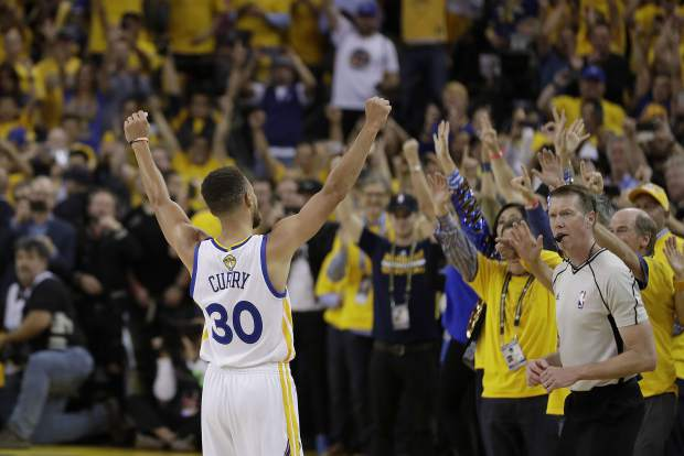Golden State Warriors guard Stephen Curry (30) celebrates with fans after Game 5 of basketball's NBA Finals between the Warriors and the Cleveland Cavaliers in Oakland, Calif., Monday. The Warriors won 129-120 to win the NBA championship.