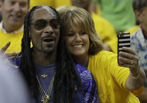 Musician Snoop Dogg, left, poses with a fan for photos before Game 5 of basketball's NBA Finals between the Golden State Warriors and the Cleveland Cavaliers in Oakland, Calif., Monday, June 12, 2017. (AP Photo/Marcio Jose Sanchez)