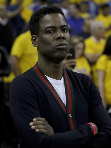 Comedian Chris Rock is shown before Game 5 of basketball's NBA Finals between the Golden State Warriors and the Cleveland Cavaliers in Oakland, Calif., Monday, June 12, 2017. (AP Photo/Marcio Jose Sanchez)
