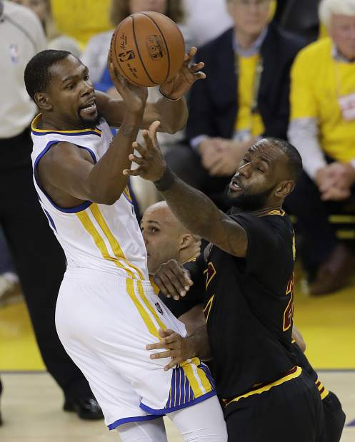 Golden State Warriors forward Kevin Durant, left, passes against Cleveland Cavaliers forward LeBron James during the first half of Game 5 of basketball's NBA Finals in Oakland, Calif., Monday, June 12, 2017. (AP Photo/Marcio Jose Sanchez)