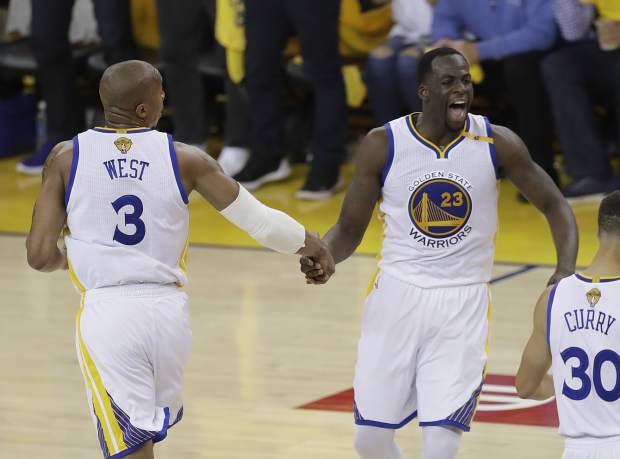 Golden State Warriors forward David West (3) celebrates with forward Draymond Green (23) during the first half of Game 5 of basketball's NBA Finals against the Cleveland Cavaliers in Oakland, Calif., Monday, June 12, 2017. (AP Photo/Marcio Jose Sanchez)
