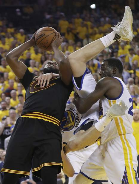 Cleveland Cavaliers center Tristan Thompson, left, shoots as Golden State Warriors guard Klay Thompson, center, is held by forward Draymond Green during the second half of Game 5 of basketball's NBA Finals in Oakland, Calif., Monday, June 12, 2017. (AP Photo/Marcio Jose Sanchez)