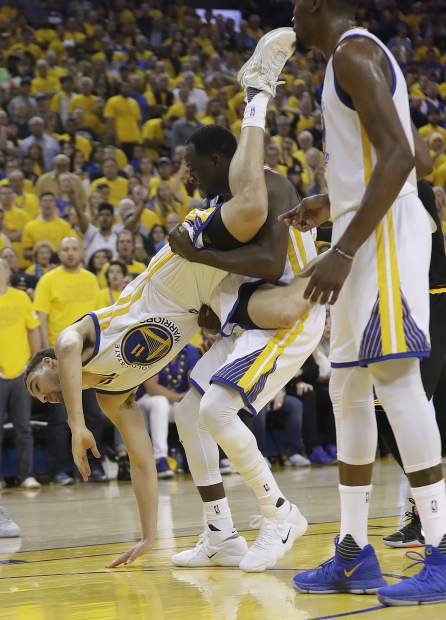 Golden State Warriors guard Klay Thompson (11) is held up by forward Draymond Green (23) during the second half of Game 5 of basketball's NBA Finals against the Cleveland Cavaliers in Oakland, Calif., Monday, June 12, 2017. (AP Photo/Marcio Jose Sanchez)